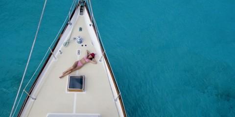 Eine Frau genehmigt sich ein Sonnenbad auf Deck
